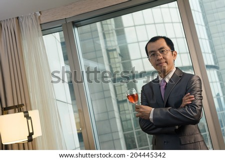Mature businessman holding a glass of wine in hotel. - stock photo