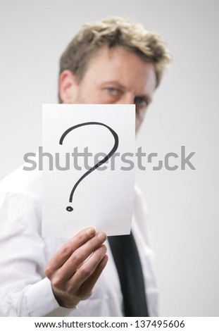 Mature businessman holding a marked placard with a question mark on it - stock photo