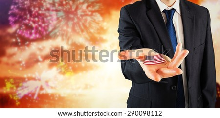 Mature businessman holding his hands out against colourful fireworks exploding on black background - stock photo