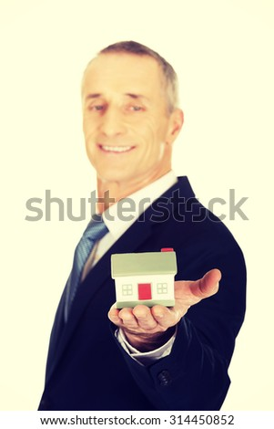 Mature businessman holding house model.