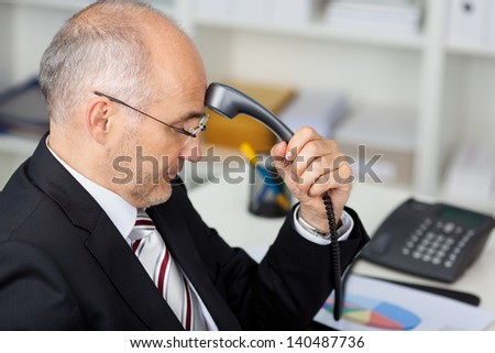 Mature businessman holding telephone receiver on his forehead - stock photo
