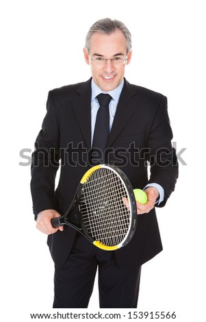 Mature Businessman Holding Tennis Racket And Ball Over White Background - stock photo