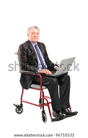 Mature businessman in a wheelchair working on a laptop isolated on white background - stock photo