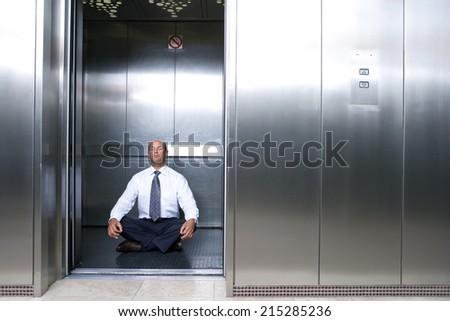 Mature businessman meditating in lift - stock photo