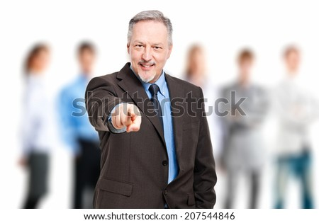 Mature businessman pointing at you - stock photo