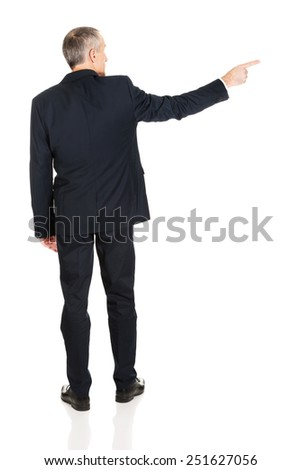 Mature businessman pointing to the right side. - stock photo