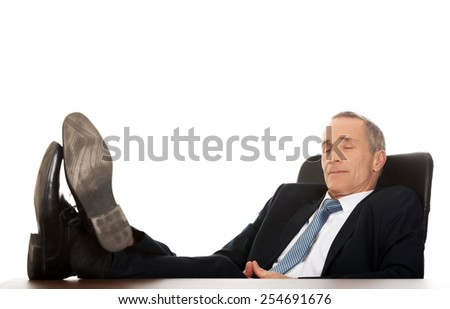 Mature businessman resting in armchair with legs up. - stock photo