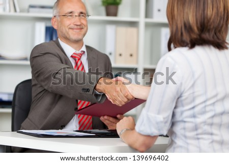 Mature businessman shaking hands with female candidate at office desk - stock photo