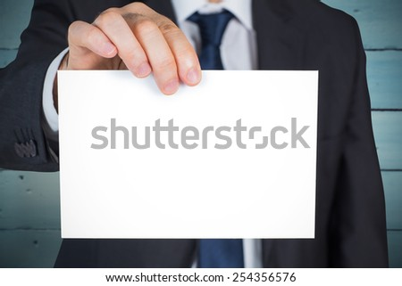Mature businessman showing card against painted blue wooden planks - stock photo