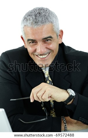 Mature businessman sitting at desk, using laptop computer, smiling. Isolated on white.? - stock photo