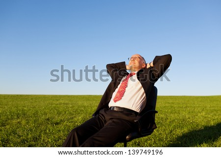 Mature businessman sitting on chair in grassy field against clear sky - stock photo