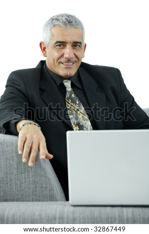 Mature businessman sitting on sofa, using laptop computer, smiling. Isolated on white.