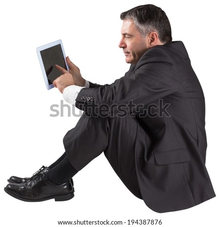 Mature businessman sitting using tablet on white background