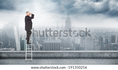 Mature businessman standing on ladder against balcony overlooking city