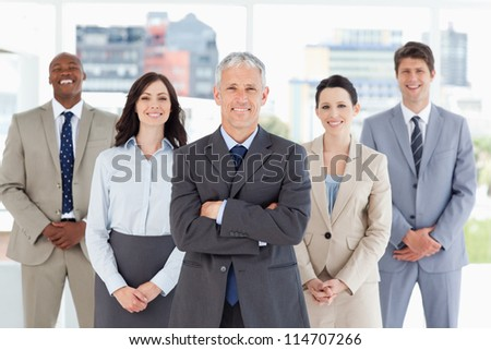 Mature businessman standing upright and crossing his arms in front of his team - stock photo