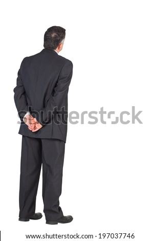 Mature businessman standing with hands behind back on white background - stock photo