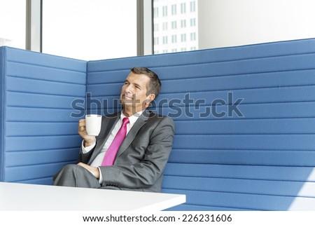 Mature businessman taking coffee break in office - stock photo