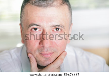 Mature businessman thinking about something and looking straight at camera - stock photo
