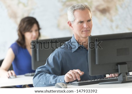 Mature businessman using computer with female colleague working in background at office