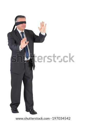 Mature businessman walking with blindfold on white background - stock photo