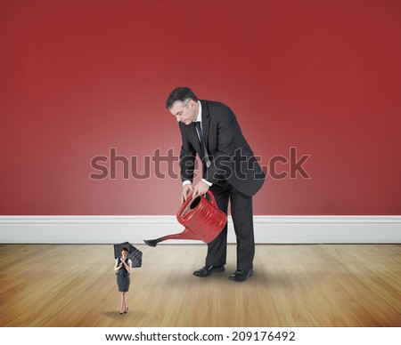 Mature businessman watering tiny businesswoman against room with wooden floor - stock photo