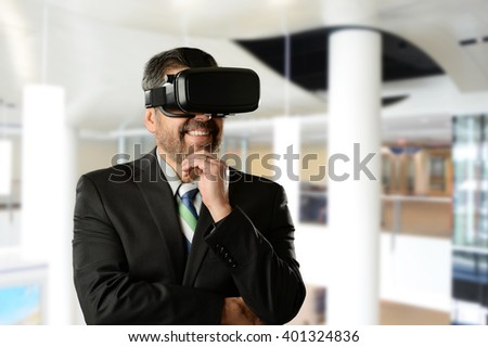 Mature Businessman wearing Virtual Reality Goggles inside an office building - stock photo