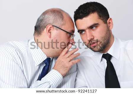 Mature businessman whisper something to his younger colleague, privacy, secret concept - stock photo