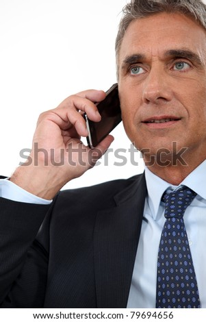 Mature businessman with a cellphone - stock photo