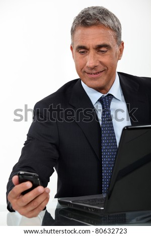 Mature businessman with a laptop and cellphone - stock photo
