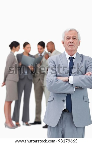 Mature businessman with arms folded and colleagues behind him against a white background - stock photo