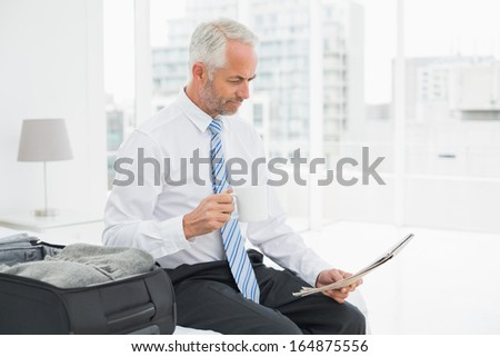 Mature businessman with coffee cup reading newspaper by luggage at a hotel room