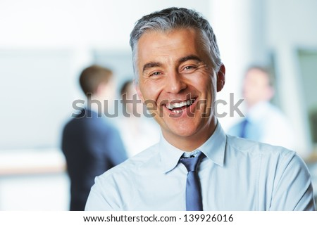 Mature businessman with colleagues in the background - stock photo
