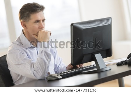 Mature businessman with hand on chin working on Desktop PC in office - stock photo
