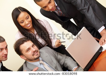Mature businessman working on laptop with his multi ethnic business team - stock photo