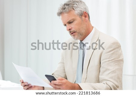 Mature Businessman Working With Papers And Cellphone At Workplace - stock photo