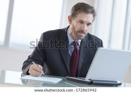 Mature businessman writing notes while using laptop at desk in office