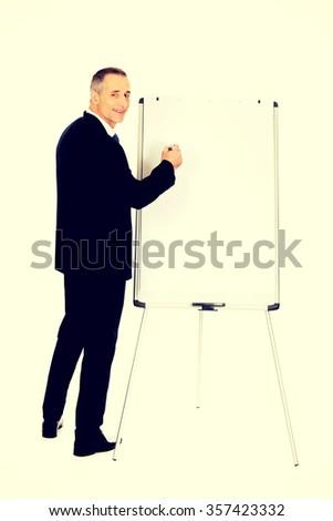 Mature businessman writing on a flipchart - stock photo