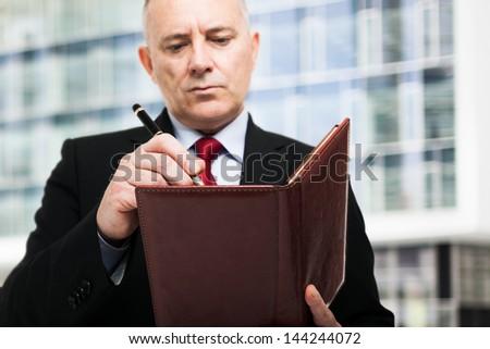 Mature businessman writing on his agenda - stock photo