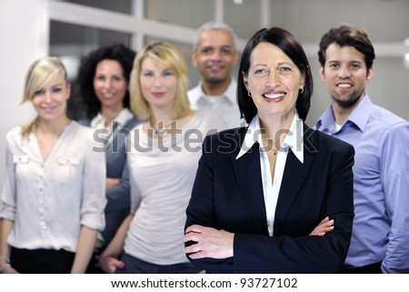 mature businesswoman and business team at office - stock photo