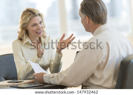 Mature businesswoman discussing with male colleague in office - stock photo