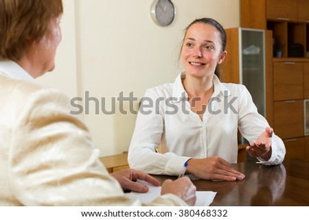 Mature businesswoman having a discussion with candidate in the office - stock photo