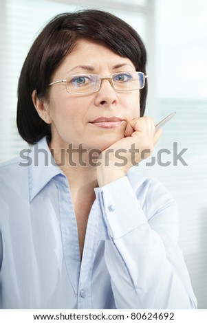 Mature businesswoman in eyeglasses looking at camera - stock photo