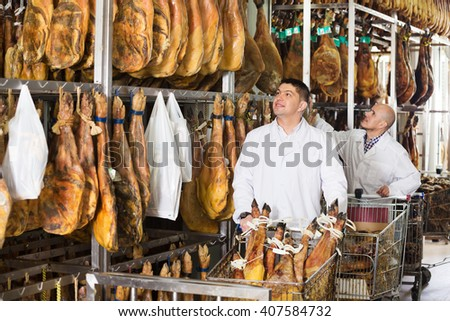 Mature butcher and his assistant with the jamon joints at meat factory. Focus on young man  - stock photo