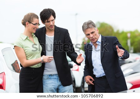 Mature car dealer and young couple standing on parking place at dealership in front of cars - stock photo