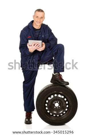 Mature car mechanic using a tablet. - stock photo