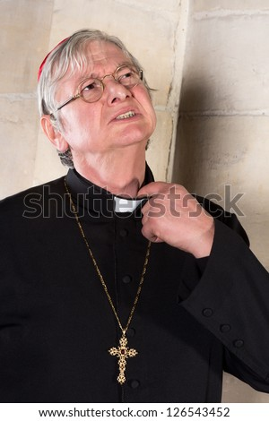 Mature cardinal annoyed by the pinching priest collar in his shirt or cassock - stock photo