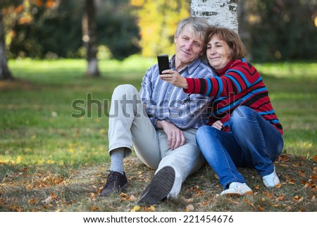 Mature Caucasian couple making selfie by cellphone in autumn park, copyspace - stock photo