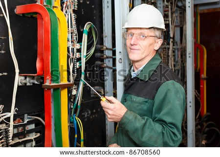 Mature Caucasian electrician worker standing in white hard hat with screwdriver in hand, looking at camera - stock photo