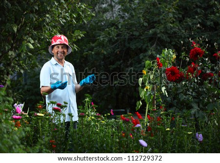 Mature caucasian happy man caring of green garden and flowers - stock photo