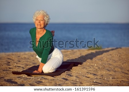 Mature caucasian woman in stretching position at beach. Senior woman doing yoga by the sea in morning - stock photo